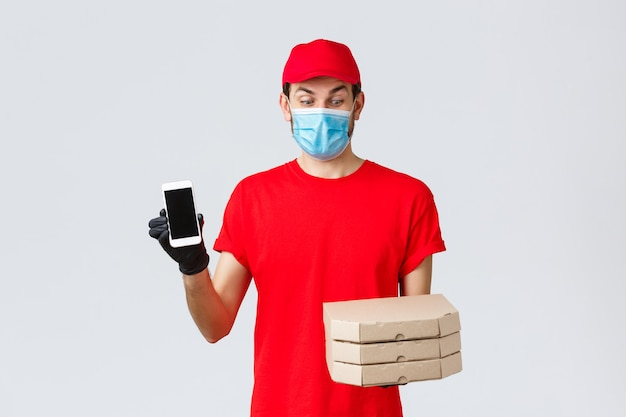 Food delivery, application, online grocery, contactless shopping and covid-19 concept. excited courier in red uniform, looking at pizza boxes amused, showing smartphone screen app or bonus promo