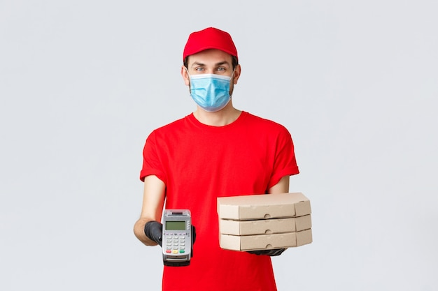 Food delivery, application, online grocery, contactless shopping and covid-19 concept. friendly courier in red uniform, face mask and gloves, holding order pizza boxes and give client pos terminal