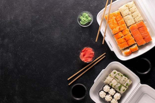 음식 배달. 검정색 배경에 플라스틱 상자에 아시아 음식