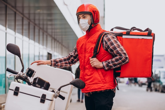 食品の入った箱でスクーターを運転し、マスクを着用した食品配達少年