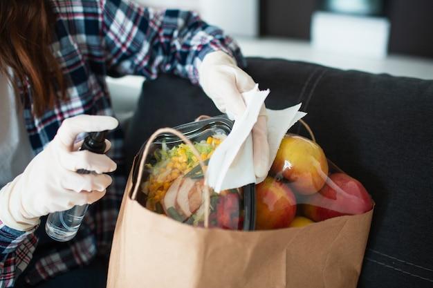 Концепция доставки еды. молодая девушка в перчатках обрабатывает антисептические средства. она пришла из продуктового магазина и принесла много еды в сумках.