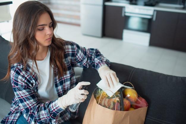 Концепция доставки еды. молодая девушка в перчатках обрабатывает антисептические препараты. она пришла из продуктового магазина и принесла много еды в сумках.