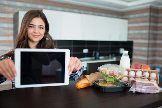 食品配達のコンセプトです。若い女性が自宅のラップトップを使用して食べ物を注文します。テーブルの上には、牛乳、箱に入ったサラダ、肉、食品、果物、卵、パン、