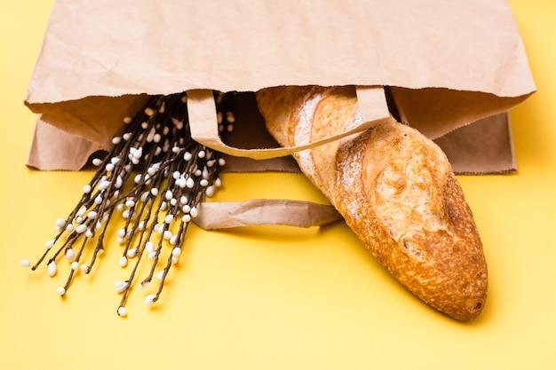 Концепция доставки еды. букет хлеба и вербы в бумажном пакете на желтом фоне