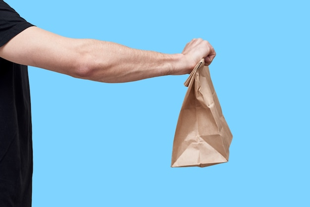 Food delivery concept. courier in black uniform hold paper bag with take away food on blue background