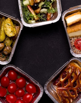 Food delivery concept. different food containers on black background.