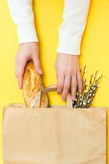 Концепция доставки еды. женские руки держат бумажный пакет с хлебом и букет вербы на желтом фоне. вертикальный вид