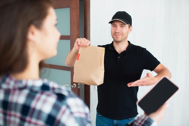 Концепция доставки еды. доставка еды человек принес еду домой к молодой женщине.