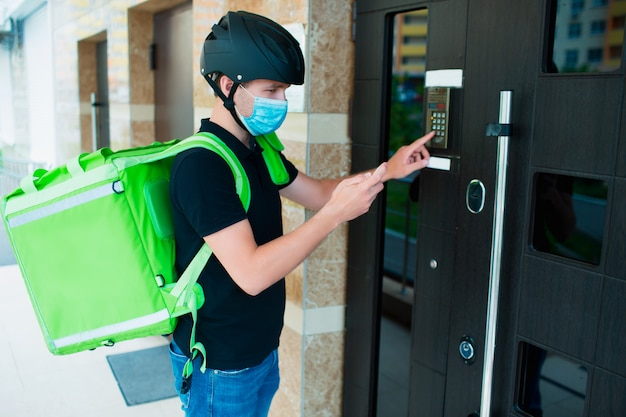 Food delivery concept. food delivery man ringing on intercom. he is wearing a medical mask