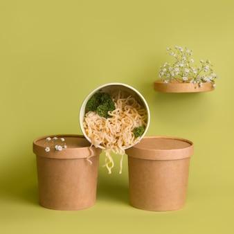 フードデリバリーのコンセプト。緑の背景にガラスの麺