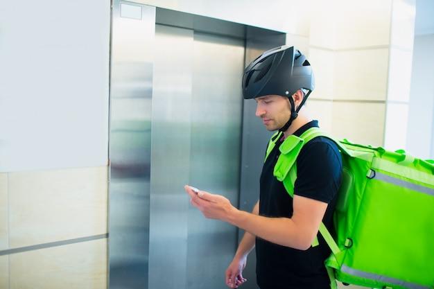 Концепция доставки еды. служащий доставки еды поднимается в лифте, чтобы найти квартиру, в которой размещен заказ.