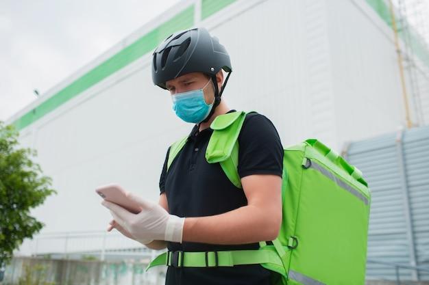음식 배달 개념. 음식 배달원은 스마트 폰을 사용하여 고객에게 더 빨리 도달합니다. 택배에는 녹색 배낭에 냉장고가 있습니다. 그는 의료 마스크와 장갑을 끼고 있습니다