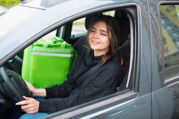 Концепция доставки еды. у женщины с доставкой еды есть зеленый рюкзак на холодильник. она сидит в машине и доставляет еду клиентам