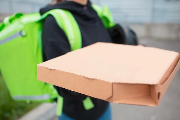 フードデリバリーのコンセプト。ピザ配達の女性は緑の冷蔵庫のバックパックを持っています。彼女はより早く配達して顧客に届けたいと思っています。彼女は私たちに食べ物を持ってきて、彼女がどのように見えるかを示します。