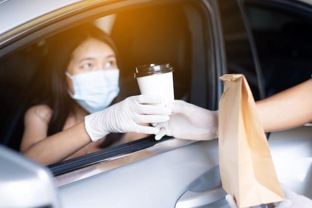 음식 배달 택배는 코로나바이러스 전염병 동안 차안의 여성에게 커피 컵을 줍니다.