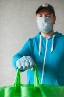 食品配達の宅配便は彼の手で布バッグを保持しています。