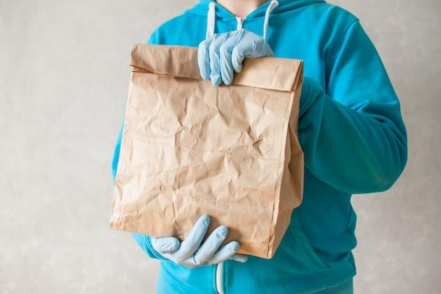 食品配達の宅配便は彼の手に大きな紙袋を保持しています。