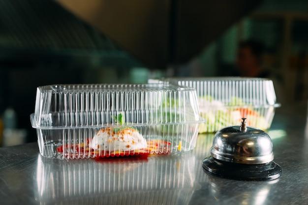 Доставка еды. раздаточный стол в ресторане с металлическим колоколом. еда в пластиковых контейнерах. панна котта и овощной салат в пластиковой одноразовой таре.