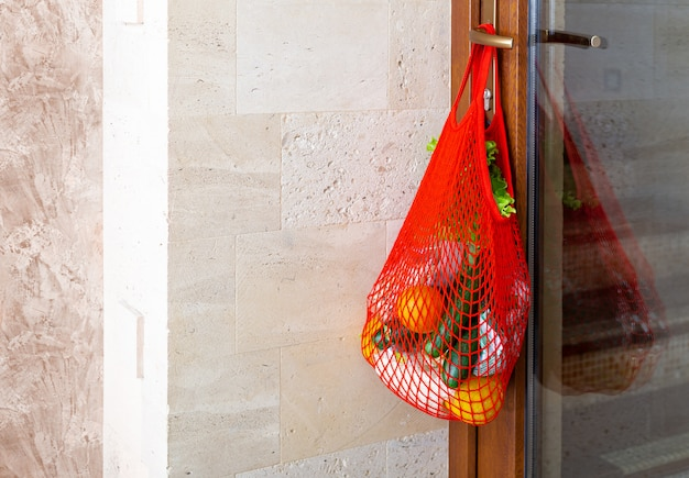 Food delivery, donation in mesh bag on door handle during covid quarantine. contactless food delivery from supermarket to home. safe shopping in coronavirus pandemic. charity donations.