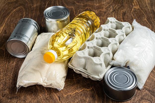 음식 배달 기부, 검역 도움말 개념. 기름, 통조림 식품, 파스타, 빵, 설탕, 계란. 나무 배경입니다. 평면도.