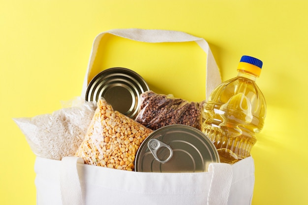 Доставка еды, пожертвование. текстильная сумка с продуктами питания на желтой поверхности. рис, гречка, горох, консервы, растительное масло, вид сверху