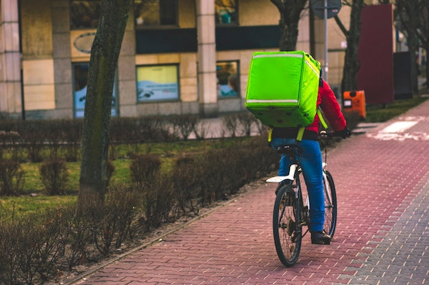 Food delivery driver with green backpack on a bicycle riding along a road