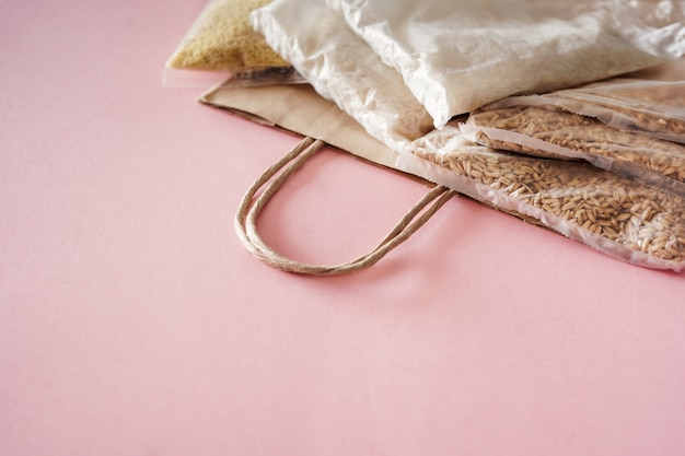 Доставка еды в период коронавируса. бумажный пакет с запасом юнитов на карантинный период изоляции, разметка на розовой стене. рис, пшено, овсянка в прозрачной сумке.