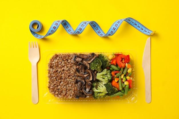食品配達。黄色の壁にテイクアウトボックスの食品。減量