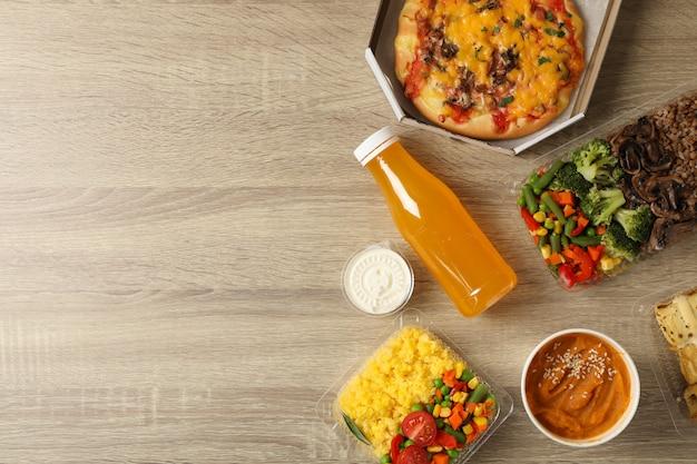 食品配達。木製のテーブルにテイクアウトボックスの食品