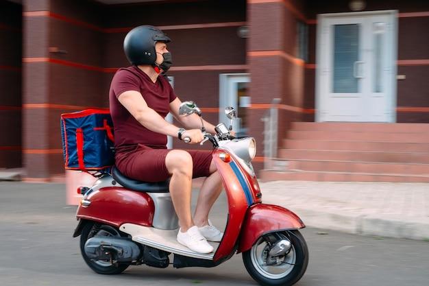 Парень из службы доставки еды на мотоцикле