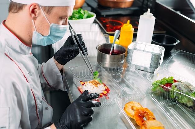 レストランでのフードデリバリー。シェフはレストランで料理を作り、使い捨ての料理に詰めます。