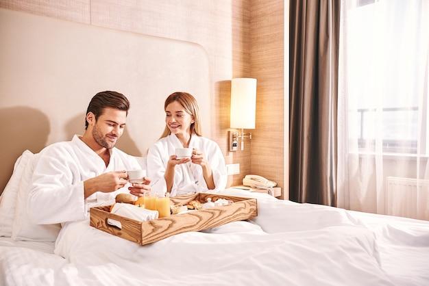 部屋での食品配達。カップルはホテルの部屋のベッドで一緒に食事をしています。ラブストーリー。ウェイターはカップルに朝食を持ってきます