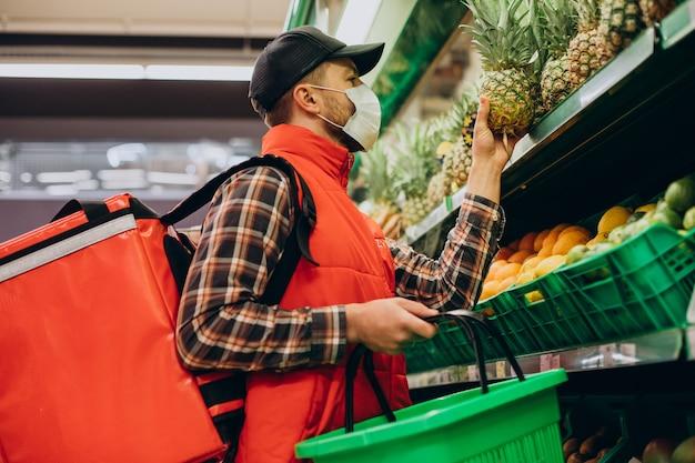 Доставщик еды покупает продукты в продуктовом магазине