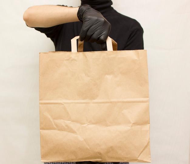 Доставка еды. человек курьер с пакетом еды