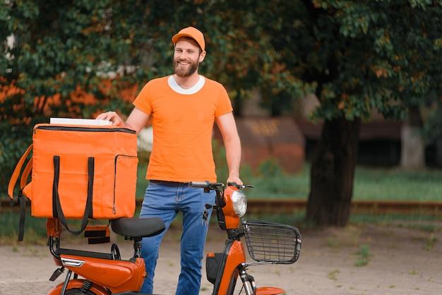 Разносчик еды в оранжевой форме стоит рядом с мопедом с сумкой для доставки еды и улыбается.