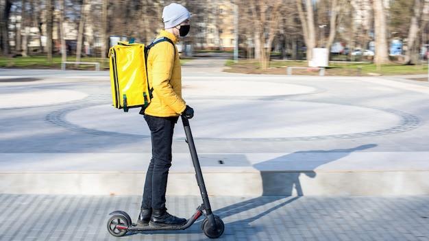 公園のスクーターで食品配達人。黒の医療用マスク、黄色のバックパックとジャケット。冬