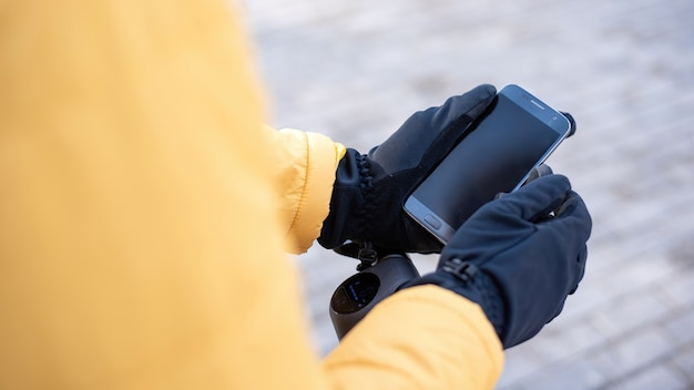 그의 스마트 폰을 사용하여 스쿠터에 음식 배달 남자. 노란색 재킷과 검은 색 장갑. 겨울