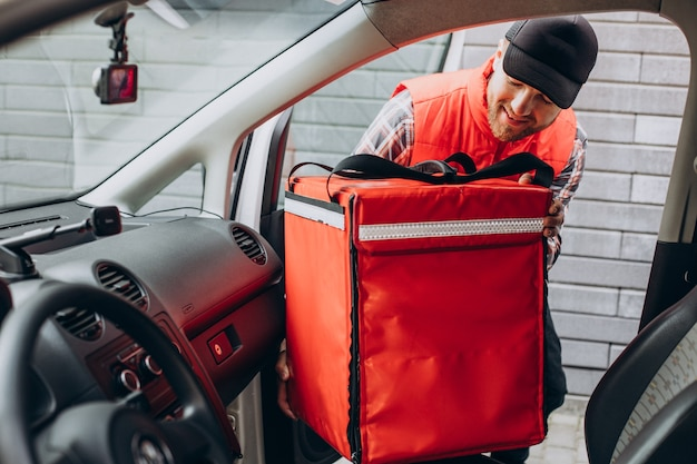 Food delivery man putting food box into a car