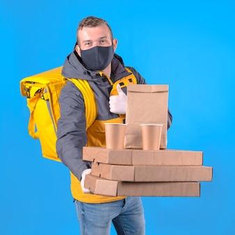 黄色いジャケットの医療マスクを持つ食品配達人