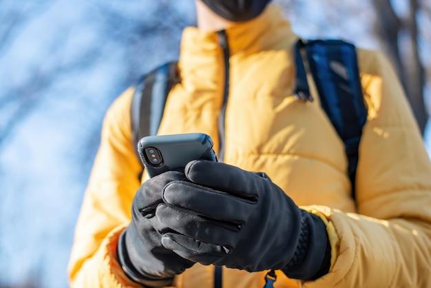그의 스마트 폰을 사용하는 배낭 음식 배달 남자. 노란색 재킷과 검은 색 장갑. 겨울