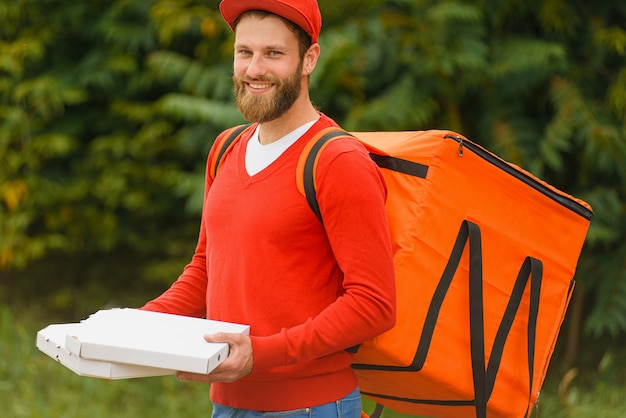 Food delivery man with food delivery bag on his back holds pizza boxes in hands and smiles