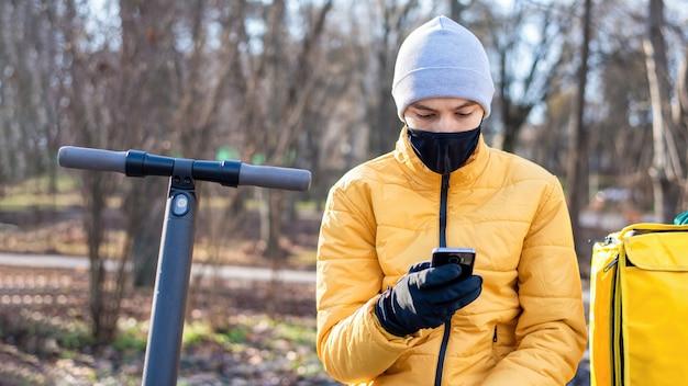 ベンチに座ってスマートフォンを使用して公園でスクーターを持った食品配達人。黒の医療用マスク、黄色のバックパックとジャケット。冬