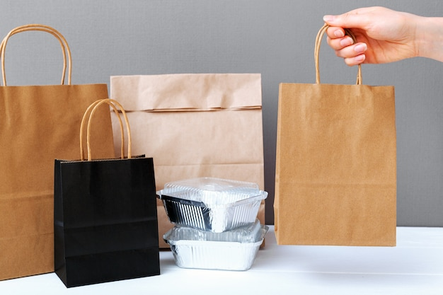 Food delivery service. brown craft paper bag package in female hand. delivery mock up packaging.