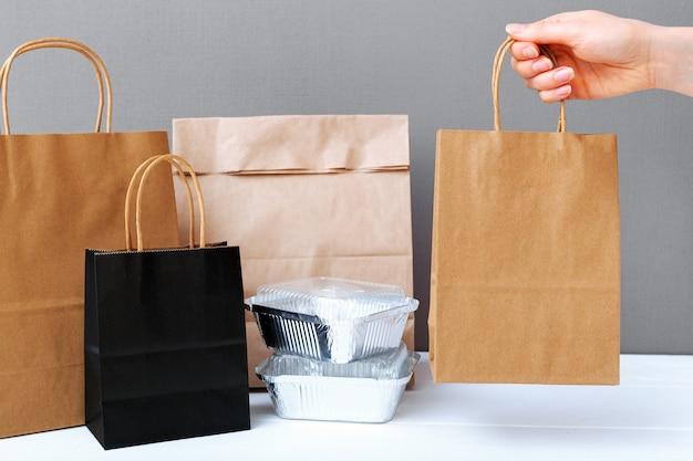 음식 배달 서비스. 여성의 손에 갈색 공예 종이 봉지 패키지. 포장은 포장을 조롱합니다.