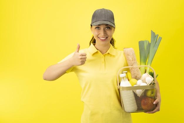 Девушка службы доставки еды с корзиной продуктов на желтой стене копией пространства