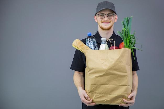 コピースペースと灰色の背景上の食料品の箱を持つ食品配達サービス男