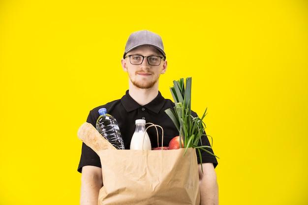 黄色の壁コピースペースに食料品の箱を持つ食品配達サービス男