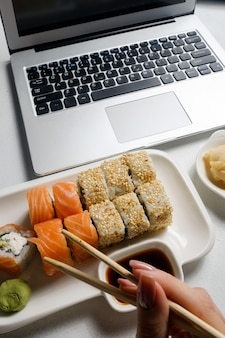 Служба доставки еды. ассорти суши роллов свежее из ресторана