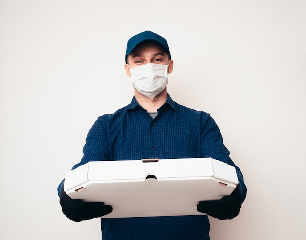 Food delivery service worker wearing a blue shirt, camp, mask and gloves in the covid-19 pandemic.