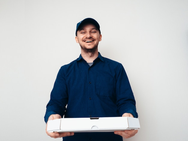 Food delivery service worker wearing a blue shirt and camp on white background.